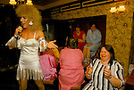 Hen party, girls only evening at the Duke of Cambridge, South London. Drag Queen artiste Candy Du Barry, real name Kevin Mahoney  telling a joke. 1980s UK.
