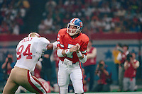 NEW ORLEANS, LA - Quarterback John Elway of the Denver Broncos is hit by San Francisco 49ers defender Charles Haley during Super Bowl XXIV at the Superdome in New Orleans, Louisiana on January 28, 1990. Photo by Brad Mangin...