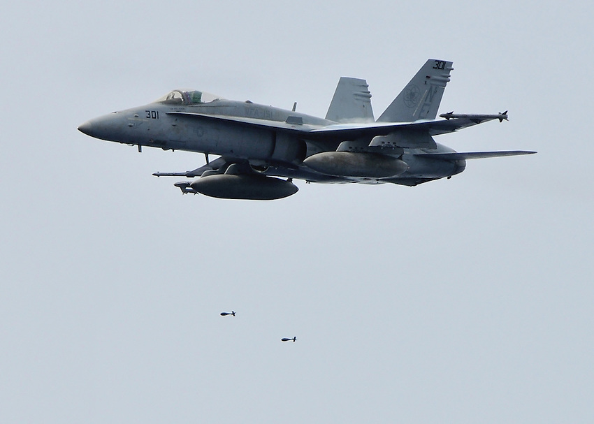 """080922-N-7981E-148 Pacific Ocean (September 22, 2008)- An F/A-18C Hornet assigned to """"Vigilantes"""" of Strike Fighter Squadron (VFA) 151 flown by Lt. Michael Apone drops a pair of MK-76 low-drag practice munitions on a target towed behind USS Abraham Lincoln (CVN 72). The USS Abraham Lincoln Strike Group is on a scheduled deployment in the U.S. 7th Fleet area of responsibility.  Operating in the Western Pacific and Indian Ocean, the U.S. 7th Fleet is the largest of the forward-deployed U.S. fleets covering 52 million square miles, with approximately 60-70 ships, 200-300 aircraft and 40,000 Sailors and Marines assigned at any given time.  U.S. Navy photo by Mass Communication Specialist 2nd Class James R. Evans (RELEASED)"""
