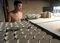 A Chinese worker carefully checks and loads clay wares before loading them into a firing oven at a porcelain workshop in Jingdezhen, Jiangxi Province, China. The township of Jingdezhen is well known in China as the country's porcelain capital ever since it was selected exactly one thousand years ago as the royal porcelain provider for the imperial court..24-JUN-04