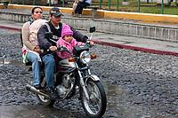 Antigua, Guatemala.  Parents on Motorbike with Two Children, no Helmet.
