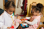 Preschool program toddler-age 2 two girls playing separately in pretend play area playing with doll and household toys