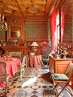 A grand dining room with an impressive coffered ceiling and patterned tiled floor. The pink and green colour scheme and floral fabrics give the room a feminine feel.
