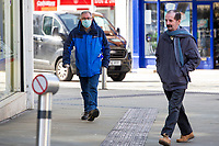 Pictured: A masked shopper walks through Swansea City Centre during the Covid-19 Coronavirus pandemic in Wales, UK, Swansea, Wales, UK. Monday 23 March 2020