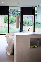 A guest bedroom features a free-standing concrete headboard and is lined with floor to ceiling windows