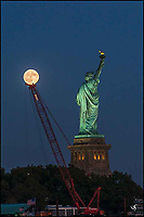 The Statue of Liberty, a crane and a full moon.