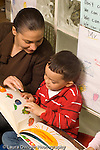 Preschool New York City ages 4-5 female parent volunteer working with boy reading book vertical