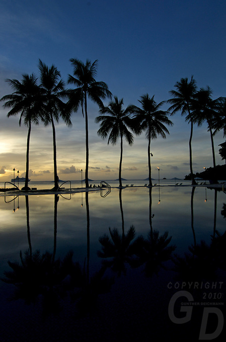 A HUGE CRUISE LINER OFF THE BEACH IN PALAU, MICRONESIA AT SUNSET, WITH THE RESORT POOL IN TE FOREGROUND