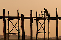 Bicyclist on U Bein bridge at sunset, Mandalay, Myanmar
