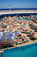 "sunbathers next to pool on board ""Song of America"" cruise ship deck. tourists."
