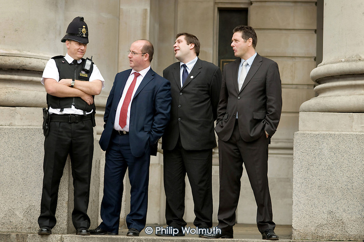 Cuty workers talk to a City of London police officer on the steps of the Royal Exchange