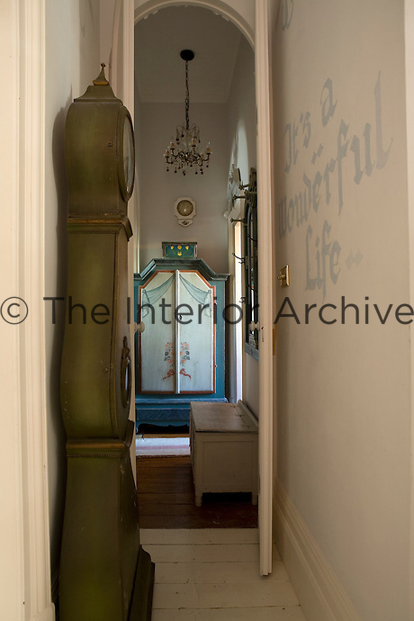 View down the hall past a green Mora clock towards a hand-painted wooden wardrobe