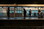 Passengers wait on Hampstead Heath London Overground station platform after dark
