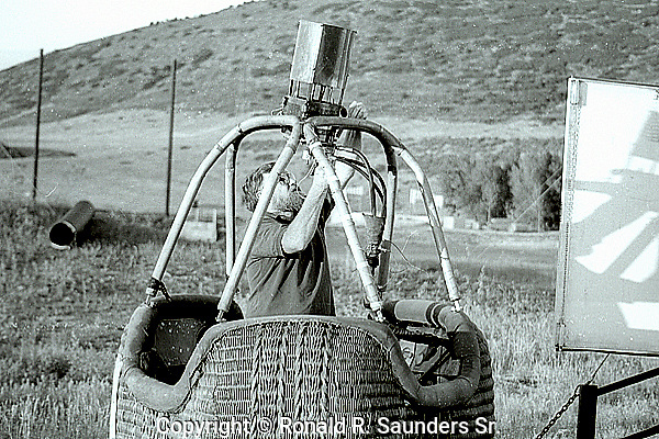 HOT AIR BALLOONIST in BASKET    PREPARES for TAKE-OFF