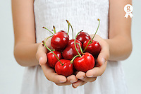 Girl (10) with red cherries in cupped hands (Licence this image exclusively with Getty: http://www.gettyimages.com/detail/102966069 )