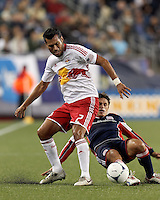 New England Revolution midfielder Ryan Guy (13) slide tackles New York Red Bulls defender Wilman Conde (2). Despite a red-card man advantage, in a Major League Soccer (MLS) match, the New England Revolution tied New York Red Bulls, 1-1, at Gillette Stadium on September 22, 2012.