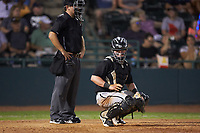Kannapolis Intimidators catcher Evan Skoug (11) looks to the dugout for the sign as home plate umpire Brandon Blome looks on during the game against the Hickory Crawdads at L.P. Frans Stadium on July 20, 2018 in Hickory, North Carolina. The Crawdads defeated the Intimidators 4-1. (Brian Westerholt/Four Seam Images)