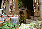 A Uighur boy minds his family's stall at a market in Kashgar, China. He is surrounded by bags of dried chiles, strings of garlic, cabbages, tomatoes and root vegetables.