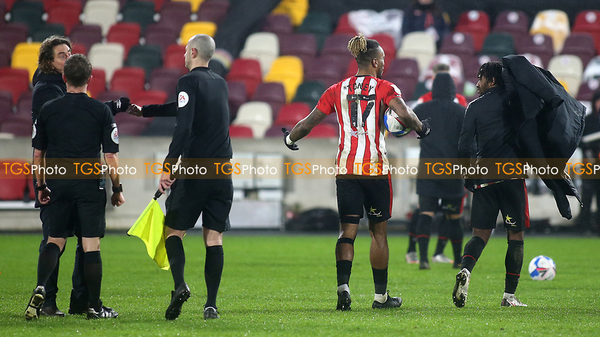 Ivan Toney of Brentford walks off the pitch with the match ball after scoring three goals as Tariqe Fosu double checks his first goal was over the line before he bundled the ball into the back of the net for Brentford's second goal during Brentford vs Wycombe Wanderers, Sky Bet EFL Championship Football at the Brentford Community Stadium on 30th January 2021