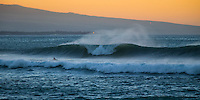 A surfer avoids a large wave breaking off Kawaihae on the Big Island at sunset.