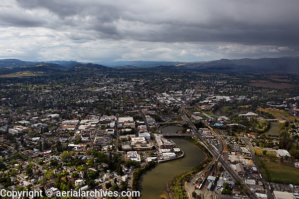 aerial photograph the City of Napa, Napa County, California from the south up the Napa Valley.  The southern terminus of the Napa Valley Wine Train is in the foreground center right of the Napa river.  Showers in the Atlas Mountains (right).