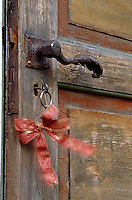 A red ribbon is tied to the key of the weathered and faded front door of a Finnish log cabin