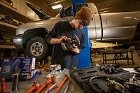 Automotive Technology student Caleb Welch works on a brake assembly during instructor Randal Smith's brake systems (ADT A150) course in UAA's Automotive and Diesel Technology Building.
