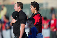 A young fan joins Kannapolis Intimidators catcher Seby Zavala (21) and home plate umpire Forrest Ladd at home plate for the National Anthem prior to the game against the Hagerstown Suns at Kannapolis Intimidators Stadium on June 15, 2017 in Kannapolis, North Carolina.  The Intimidators defeated the Suns 9-1 in game two of a double-header.  (Brian Westerholt/Four Seam Images)