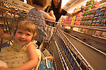 young girl sitting in grocery cart smiling while mother chooses items from shelf, parenting