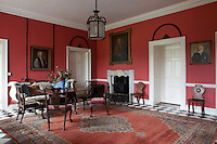 The red-painted entrance hall is furnished with an Irish mahogany table and chairs, probably original to the house