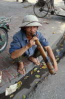 Mann mit Bambuspfeife in Hanoi, Vietnam