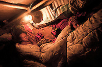 A Kachin refugee family sleep as they lay down inside a tent at Je Gau Pa IDP camp, located at the high mountains of northeastern Kachin State. This is one of the most remote temporary shelters settled under tough and poor conditions. The camp gives shelter to two thousand displaced persons from the war-torn villages close to Maiya Jang city. The KIA positions around the city have been attacked by shelling and heavy artillery during months. Fierce clashes have taken place since the ceasefire was broken out by the Burmese army last June 2011. During months the fighting were spread out along the Kachin State leaving more than 40,000 displaced persons and refugees (a conservative estimating) in accord with the humanitarian aid groups.