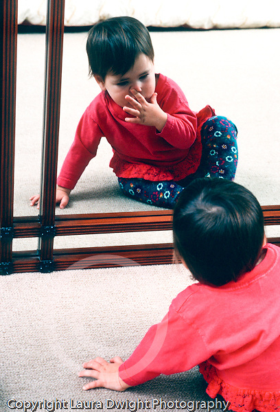 Toddler girl 18 months old looking at own reflection in mirror touching her nose with finger recognizing self vertical Caucasian
