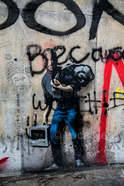 """Banksy: """"The Son of a Migrant from Syria"""" (Steve Jobs).<br /> <br /> Calais Jungle Camp.<br /> <br /> Under the Sky of Calais & Dunkirk. Two Camps, Two Sides of the Same Coin: Not 'migrants', Not 'refugees', just Humans.<br /> <br /> France, 24-30/03/2016. Documenting (and following) Zekra and her experience in the two French camps at the gate of the United Kingdom: Calais' """"Jungle"""" and Dunkirk's """"Grande-Synthe"""". Zekra lives in London but she is originally from Basra in Iraq. Zekra and her family had to flee Kuwait - where they moved for working reason - due to the """"Gulf War"""", and to the Western Countries' will to """"export Democracy in Iraq"""". Zekra is a self-motivated volunteer and founder of """"Happy Ravers"""", a group of people (not a NGO or a charity) linked to each other because of their love for rave parties but also men and women who meet up every week to help homeless people and other people in need in Central London. (Here there are some of the stories I covered about Zekra and """"Happy Ravers"""": http://bit.ly/1XVj1Cg & http://bit.ly/24kcGQz & http://bit.ly/1TY0dPO). Zekra worked as an English teacher in the adult school at Dunkirk's """"Grande-Synthe"""" camp and as a cultural mediator and Arabic translator for two medic teams in Calais' """"Jungle"""". Please read her story at the beginning of this reportage."""