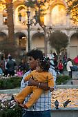 Arequipa, Peru. Plaza de Armas (public square). Father (Peruvian) holds baby girl (Peruvian) in the plaza. No MR. ID: AL-peru.