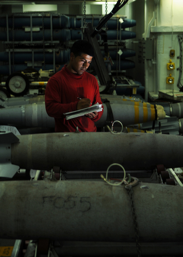 080530-N-7981E-220 ARABIAN GULF (May 30, 2008)- Aviation Ordnanceman 3rd Class Victor Samaguey, assigned to Weapon's Department's G-3 Division, completes a breakout and reconfiguration sheet on a GBU-12 laser guided bomb inside a weapons magazine aboard Nimitz-class aircraft carrier USS Abraham Lincoln (CVN 72). Lincoln is deployed to the U.S. Navy 5th Fleet area of responsibility to support Maritime Security Operations (MSO).  MSO help develop security in the maritime environment, which promotes stability and global prosperity.  These operations complement the counterterrorism and security efforts of regional nations and seek to disrupt violent extremists' use of the maritime environment as a venue for attack or to transport personnel, weapons or other material.  U.S Navy photo by Mass Communication Specialist 2nd Class James R. Evans (RELEASED)