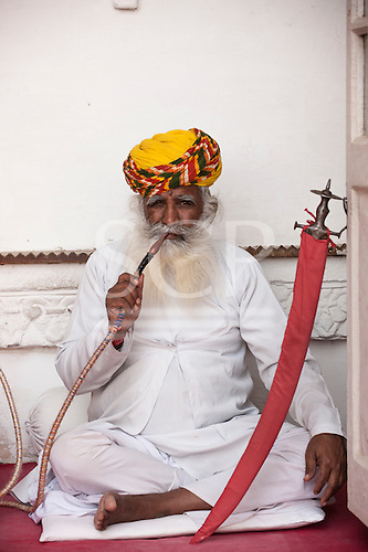 Jodhpur, India. Mehrangarh sandstone hill fort of the Marwar rulers. A man in traditional clothes smoking a hookah water pipe.
