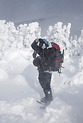 A hiker photographing along the Appalachian Trail (Carter-Moriah Trail) near the summit of Carter Dome in Bean's Purchase in the New Hampshire White Mountains during a windy winter day.