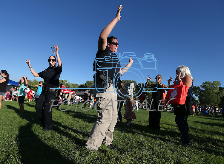 Washoe Tribal Officers Savannah Gray, left, and Ruby Fox do the Hokey Pokey with the crowd during the 14th annual National Night Out in Carson City, Nev., on Tuesday, Aug. 2, 2016. <br />Photo by Cathleen Allison