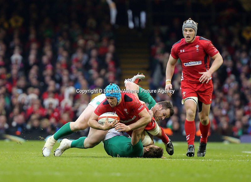 Pictured:Justin Tipuric of Wales (in red) is brought down by Cian Healy and Eoin Reddan of Ireland Saturday 14 March 2015<br /> Re: RBS Six Nations, Wales v Ireland at the Millennium Stadium, Cardiff, south Wales, UK.