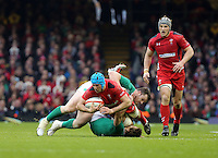 Pictured:Justin Tipuric of Wales (in red) is brought down by Cian Healy and Eoin Reddan of Ireland Saturday 14 March 2015<br />