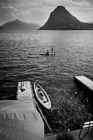 Switzerland. Canton Ticino. Lugano. Hot summer day. Private beach belonging to Hotel Lido Seegarten. A woman is sunbathing on a wooden pier. A father and his son enjoys a stand up paddle ride on the lake. Stand up paddleboarding (SUP) or Stand up paddle surfing is an offshoot of surfing. Stand up paddle boarders stand on their boards and use a paddle to propel themselves through the water. Lake Lugano (or Ceresio Lake) is a glacial lake. The Monte San Salvatore (912 m) is a mountain in the Lepontine Alps above Lake Lugano and the city of Lugano. 6.07.2020 © 2020 Didier Ruef