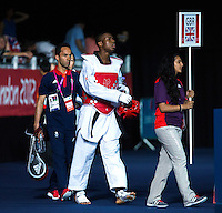 10 AUG 2012 - LONDON, GBR - Lutalo Muhammad (GBR) (centre) of Great Britain, followed by coach Joseph Salim, walks to the mat before his men's -80kg category preliminary round contest against Farkhod Negmatov of Tajikistan during the London 2012 Olympic Games Taekwondo at Excel in London, Great Britain .(PHOTO (C) 2012 NIGEL FARROW)