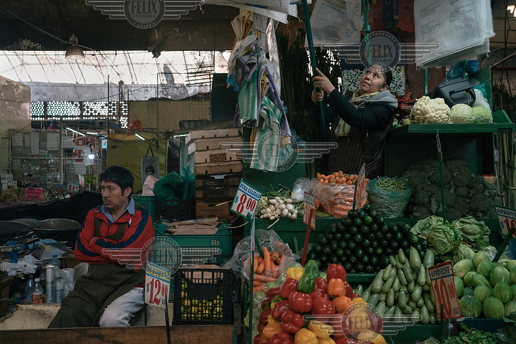 Ines Conofre Bernal (39), a single mother of two boys, working at her vegetable stand in La Marced market. ''There's no women's day for us, no resting day'', she says in reference to the national women's strike, 'A Day Without Women'.