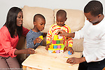 Family at home playing game with balancing blocks, mother and father with sons ages 5 and 3