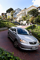 Tourists driving down Lombard Street the windiest street in the world as the curve and winding angles of this famous landmar