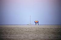 Capo Carbonara, Villasimius (Cagliari), Porto Giunco. Una barca a vela, due bagnanti e un ombrellone colorato sulla spiaggia verso sera --- Cape Carbonara, Villasimius (Cagliari), Porto Giunco. A sailing boat, two bathers and a colorful umbrella on the beach towards the evening