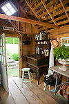 Inside the garden shed on the property behind the farmhouse, a utilitarian space has been transformed into a garden hideaway complete with sitting area, woodstove, antique display cabinets for garden trinkets, a potting bench, and a work desk for recording the seasonal changes.  The attached greenhouse was salvaged from a local arboretum and restored for use here, and adds to the romantic, cottage garden feel of the white garden just outside, while also separating the orchard and vegetable gardens wich lie behind the shed. Garden design by Toni Christianson, Christianson's Nursery