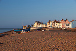 Great Britain, England, Suffolk, Aldeburgh: View along pebble beach to fishing boats and town at dawn
