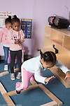 Education preschool 3-4 year olds group of girls playing jumping game made from blocks in classroom, two girls waiting for their turn to jump
